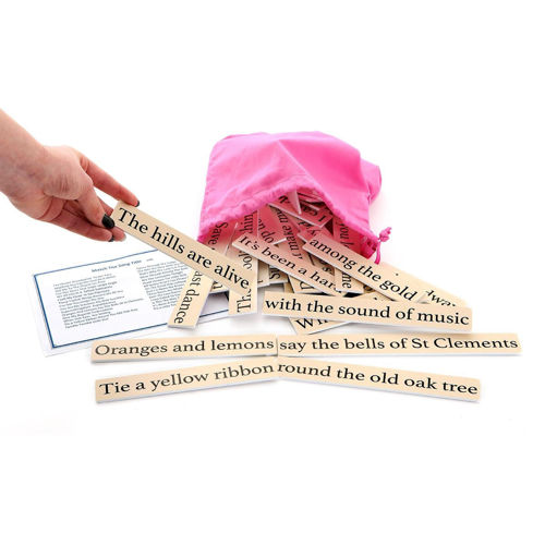 Match the Song Titles Set 1, image shows pink cotton bag with drawstring with tiles spilling out, hand is holding a tile that reads 'The Hills Are Alive' in bold print with a white background, Set includes: 30 sayings to match on durable plastic with large print lettering. Answer card. Drawstring storage bag.  Size: Tiles: (l) various x (w) 3cm x (h) 0.3cm. Bag: (l) 33cm x (w) 24cm.