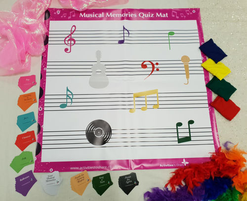 Musical Memories Floor Mat & Question Card Game, image shows pink and white mat with coloured category question cards displayed around and 4 x bean bags on the side. Set includes: Wipe clean PVC mat, 4 x cotton (bean filled) bean bags, 110 question cards and instructions/guide sheet.  Size:approx. Mat: (l) 95cm x (w) 95cm. Bean bags: approx: (l) 13cm x (w) 11cm.