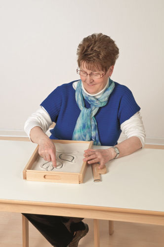 Lady drawing pattern in sand tray