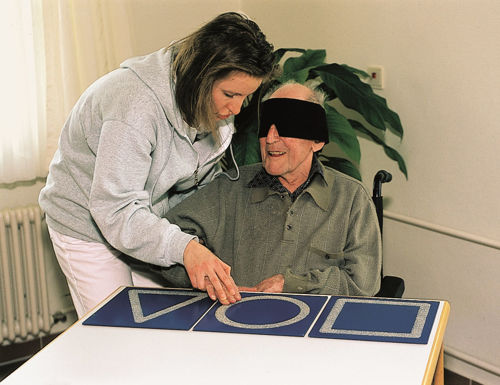 Lady and blind folded old man playing sensory game
