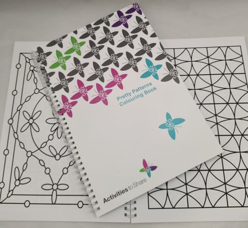 Large Print Pretty Patterns Colouring Book, dementia friendly activity book also sight impaired, large bold outlines to colour, cover of book shows white background with butterfly designs in pink blue green and black, 2 design pages in background, size: A4 spiral-bound softback book